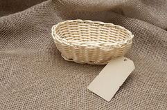 Empty wicker basket on the background fabric. New wicker basket on the background of burlap royalty free stock images