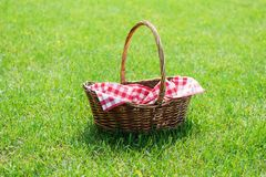 Empty wicker basket with red tablecloth on green grass in a park. Copy space stock image