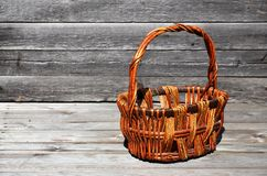 An empty wicker basket of wooden rods lies on a wooden surface. Against the background of a wall of black horizontal wooden boards. Patterned brown hand-made stock image