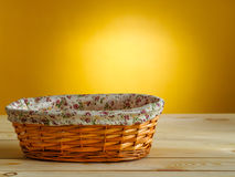 Empty wicker basket on yellow background. Empty wicker basket on wooden table Royalty Free Stock Image