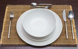 Empty wihte dinner plates and utensils on dark wooden dining tab Stock Photography