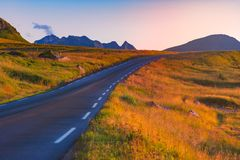Empty road in Norway, Europe. Sunset travel. Empty winding country road in Norway, Europe, Scandinavia. Auto travel on sunset. Blue sky with clouds Royalty Free Stock Photo
