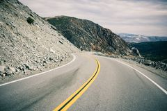 An empty winding road in Death Valley. A thin yellow line in the middle of an empty road winding through Death Valley in Arizona stock image