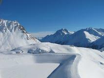 Empty winding ski run on sunny winter day. Austrian alps Stock Photo