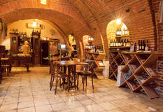 Empty wine bar inside the old brick underground with restaurant furniture and wine bottles royalty free stock photography