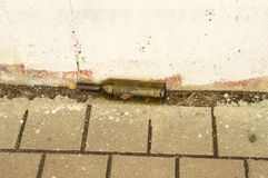 Empty wine bottle lying on the street. Background royalty free stock image