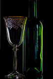 Empty Wine Bottle And Red Wine Glass On Black Background. Close-Up Royalty Free Stock Image