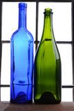 Empty Wine Bottle Still Life. A blue and a green wine bottle in front of a window Royalty Free Stock Images