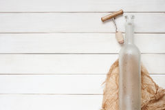 Empty wine bottle on the wooden background. Empty wine bottle on the white wooden background Stock Image
