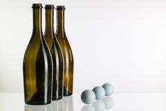 Empty wine bottles and golf balls Royalty Free Stock Photos
