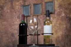 Empty wine glass infront of wine bottles Stock Images