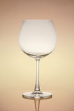 Empty wine glass  on orange background Royalty Free Stock Photo