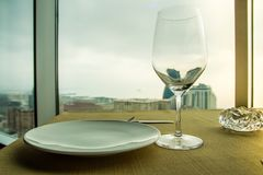 Empty wine glass on the table in front of a window. Close up shot Royalty Free Stock Photo