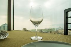 Empty wine glass on the table in front of a window. Close up shot Stock Photography
