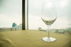 Empty wine glass on the table in front of a window. Close up shot Stock Photos