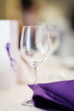 Empty wine glass on the table. An empty glass sitting on a restaurant table near a purple napkin Stock Image
