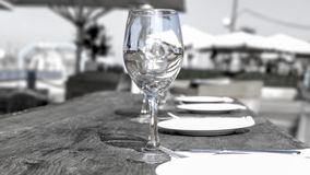 Empty wine glass on a wooden table in a cafe on a city beach. Israel royalty free stock image
