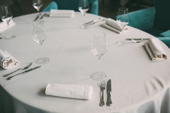 Empty wine glasses arranged on a table in an open air restaurant or bar. Stock Photos