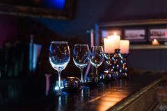 Empty wine glasses and candles with illumination lights background royalty free stock photos
