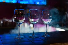 Empty wine glasses in row on bar or restaurant royalty free stock image