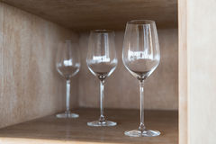 Empty wine glasses set on shelf at restaurant Stock Photo