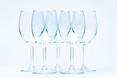 Empty wine glasses stand symmetrically on white Stock Image