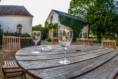 Empty wine glasses on a table, French Chateau. A pair of wine glasess sits on a wooden porch table outside a chateau near Le Mans, France glows a dusk in summer Royalty Free Stock Photo