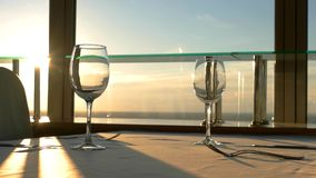 Empty wineglasses on the table. Sunset sky behind the window. Expensive restaurant in Vilnius. Surprise for your loved ones stock footage