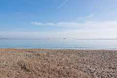 Empty winter beach Ibiza. Empty beautiful sandy Playa d'en Bossa beach on a sunny and misty winter morning in December in Ibiza, Spain Royalty Free Stock Photo
