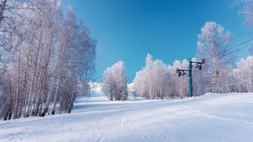 Empty winter sport resort view with snow, trees and blue sky. Old winter sport resort in Russia. Empty winter sport resort view with snow, trees and blue sky Stock Images