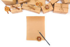 Empty Wish list for christmas and kraft paper decorated presents on a white Stock Photos