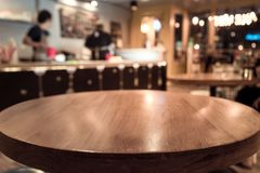 Empty wod table top with blur of people in coffee shop/cafe Royalty Free Stock Images