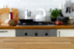 Empty wood counter in front of out of focus home kitchen backgro. Und Stock Image