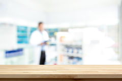 Empty wood counter top on blur pharmacy background. Empty wood counter top on blur pharmacy chemist shop or drugstore background stock image