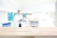 Empty wood counter top on blur pharmacy background. Empty wood counter top on blur pharmacy chemist shop or drugstore background Royalty Free Stock Photos