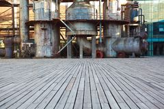 Empty wood floor road surface with old steel steelworks of pipelines Stock Images