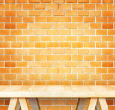 Empty wood modern table and grunge orange brick wall in backgrou Royalty Free Stock Image