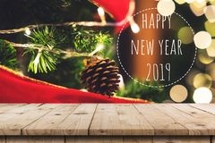 Empty wood table and christmas pine cones hanging on Christmas tree and Happy New Year 2019 with display montage for product.  royalty free stock photos