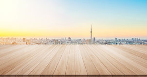 Empty wood table  floor top for display or montage product. Empty wood table top on panoramic modern cityscape building under sunrise and morning blue bright sky Royalty Free Stock Image