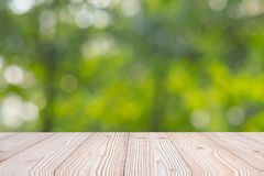 Empty wood table on green natural background in the garden outdoor. Mock up for your product display or montage royalty free stock photo