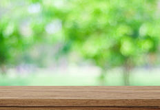 Empty wood table over blurred trees with bokeh background Stock Photos