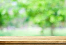 Empty wood table over blurred trees with bokeh background. Product display montage royalty free stock image