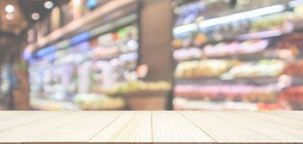 Empty wood table top with Supermarket background. Empty wood table top with abstract blur fresh organic fruits and vegetables on shelf in grocery store defocused stock photos