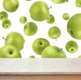 Empty wood table on background of flying green apples. Empty of wood table top on the background of flying green apples. For montage product display or design Stock Photography
