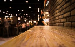 Empty wood table top of bar with blur of cafe restaurant in dark Stock Photos