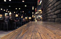 Empty wood table top on blur cafe restaurant in dark background Stock Photos