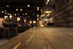 Empty wood table top on blur cafe restaurant in dark background. /selective focus .For montage product display royalty free stock photos