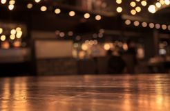 Empty wood table top and  blur of cafe restaurant in dark  night Stock Images