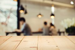 Empty wood table top with blur of people in coffee shop. royalty free stock image