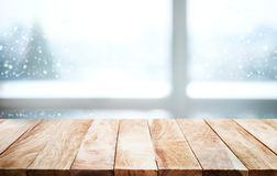 Wood table top with snowfall of winter season background.christmas. Empty wood table top on blur window view with pine tree in snow of winter season background Royalty Free Stock Images